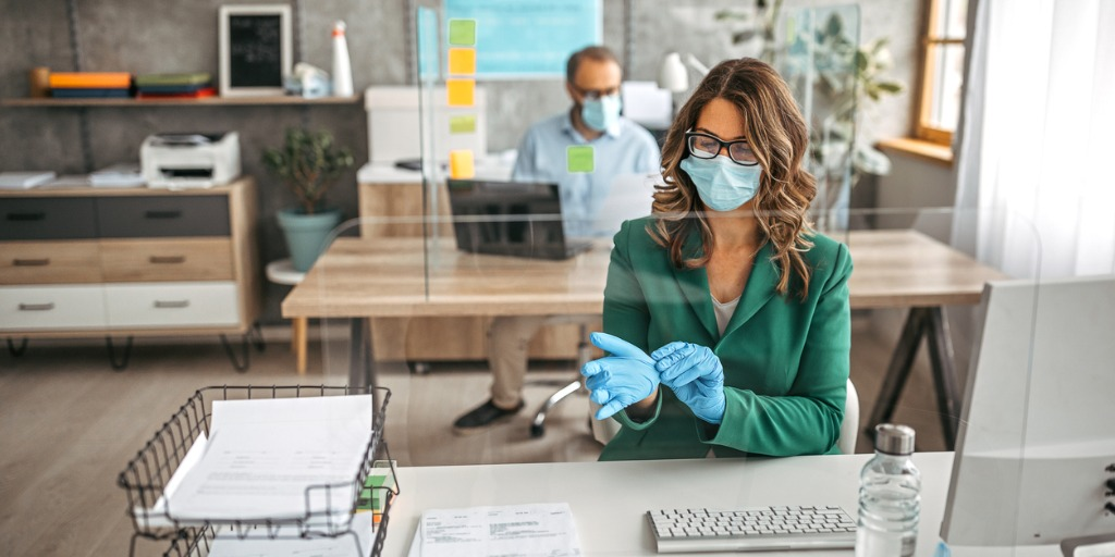 businesswoman-putting-on-protective-gloves-in-the-office-picture-id1241932606