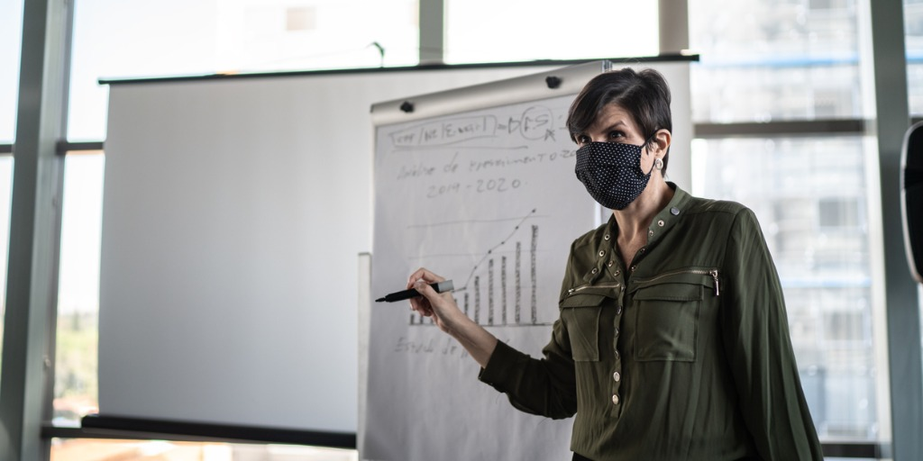 businesswoman-speaking-at-a-business-conference-with-face-mask-picture-id1257195590