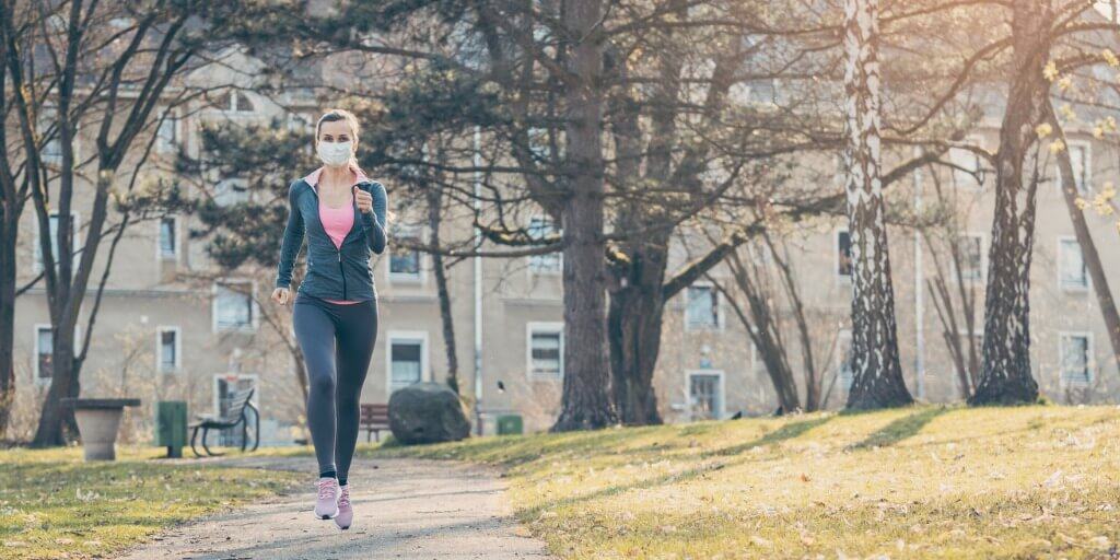 woman-jogging-down-a-path-boosting-her-immune-system-for-covid19-picture-id1214245205
