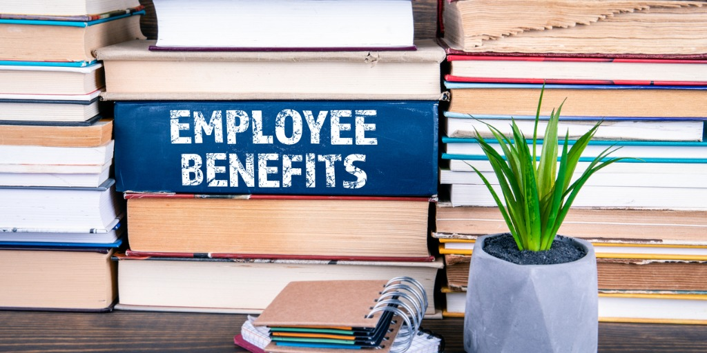 employee-benefits-concept-books-stacked-on-table-picture-id1141673229