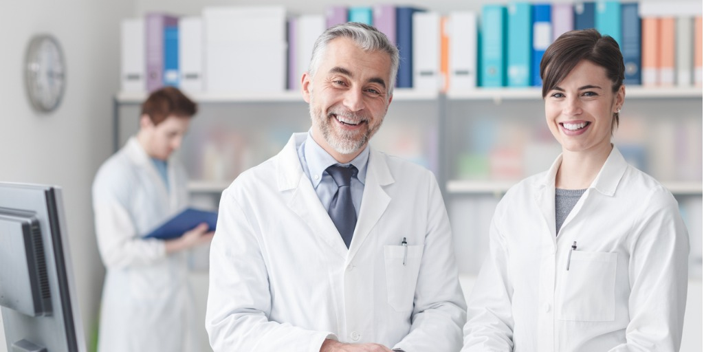doctor-at-the-reception-desk-with-his-assistant-picture-id584211964