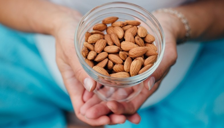 woman holding container of almonds